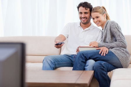 In love couple watching TV while eating popcorn in their living room Stock Photo - 11682955