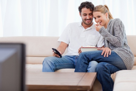 Charming couple watching TV while eating popcorn in their living room Stock Photo - 11682994