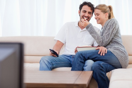 Lovely couple watching TV while eating popcorn in their living room photo