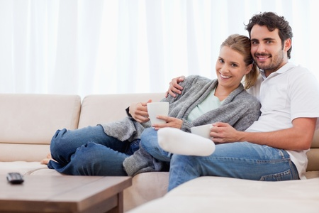 Couple having a cup of tea in their living room photo