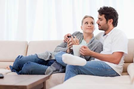 Couple having a cup of coffee in their living room photo