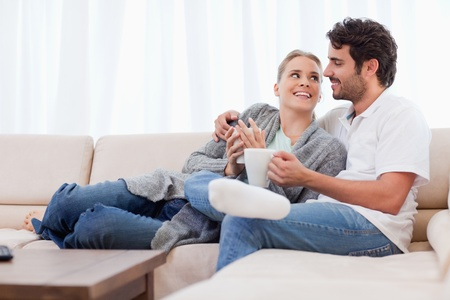 Young couple having a cup of coffee in their living room photo