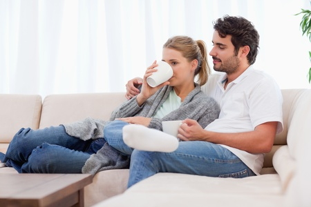 Young couple having a cup of tea in their living room Stock Photo - 11684684