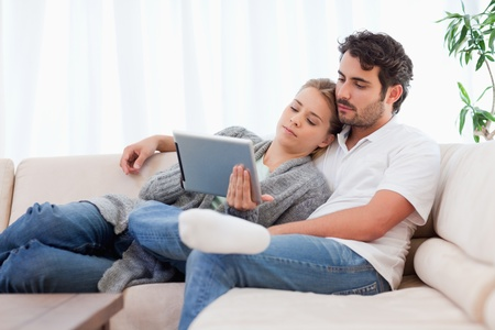 cocooning: Lovely couple using a tablet computer in their living room