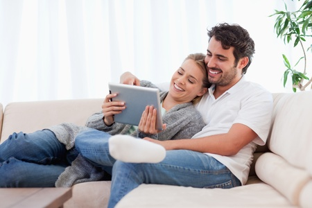 In love couple using a tablet computer in their living room photo