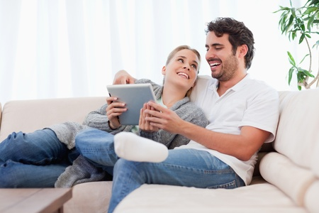delighted: Delighted couple using a tablet computer in their living room