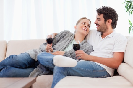 Young couple having a glass of red wine in their living room photo