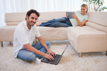 Woman using a tablet computer while her boyfriend is using a notebook in their living room photo
