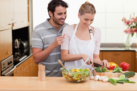 slicing: Couple slicing vegetables in her kitchen