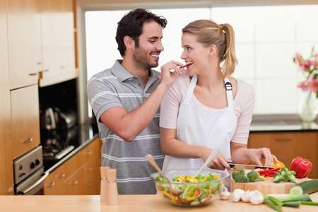 cuchillo de cocina: Encantadora pareja cocinar en su Kichen