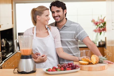 Couple making fruits juice in their kitchen photo