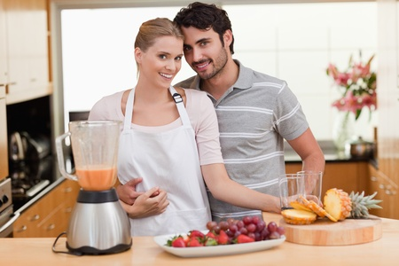 Couple making fresh fruits juice in their kitchen photo