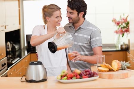 desayuno romantico: Pareja joven haciendo jugo de frutas frescas en la cocina Foto de archivo