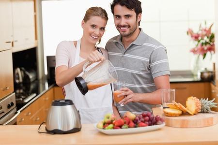 licuadora: Pareja joven haciendo el jugo de las frutas en la cocina
