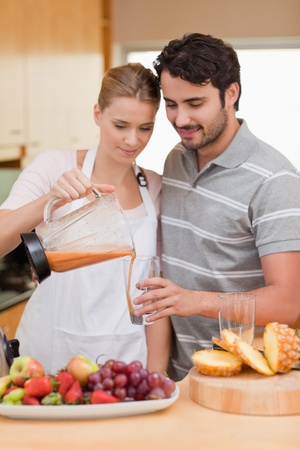Portrait of a couple drinking fruits juice in their kitchen photo