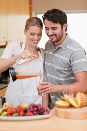 Portrait of a young couple drinking fruits juice in their kitchen photo
