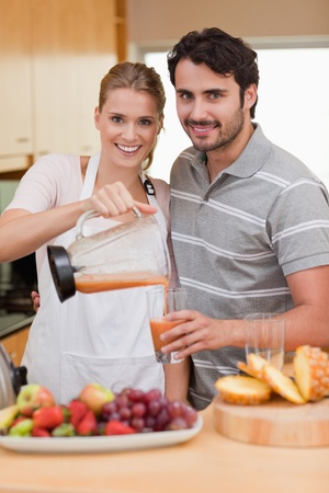 Portrait of a smiling couple drinking fruits juice in their kitchen photo