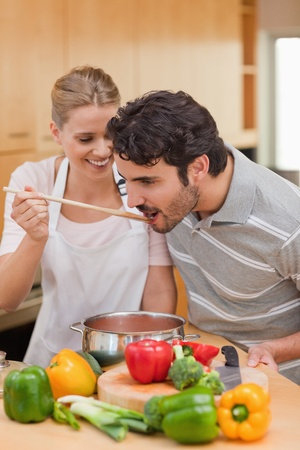 Portrait of a young couple preparing a sauce in their kitchen photo