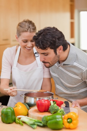 Portrait of a happy couple preparing a sauce in their kitchen photo