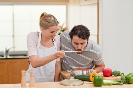 Couple preparing a sauce in their kitchen photo