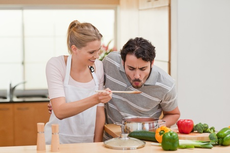 Young couple preparing a sauce in their kitchen photo