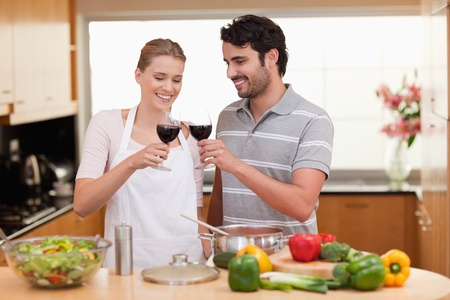 Couple drinking a glass of wine in their kitchen photo