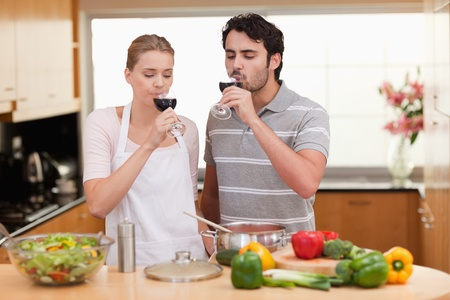 Young couple drinking a glass of wine in their kitchen photo
