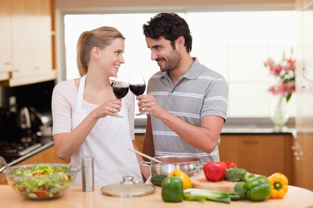 Lovely couple drinking a glass of wine in their kitchen photo