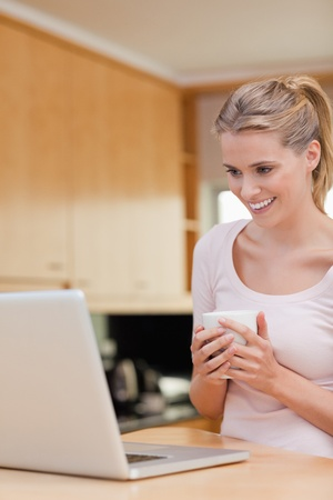 Portrait of a young woman using a laptop while drinking coffee in her kitchen photo