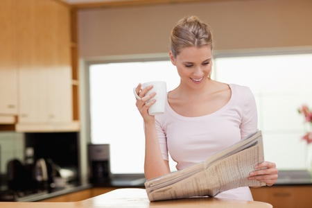 Woman reading the news while having tea in her kitchen photo