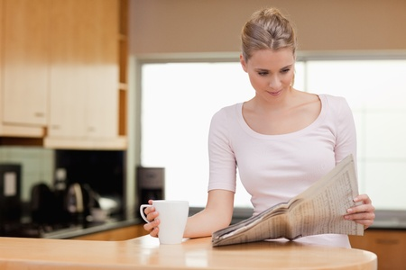 woman reading: Young woman reading the news while having tea in her kitchen