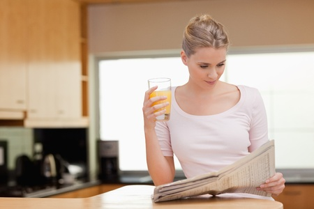 Woman reading the news while drinking orange juice in her kitchen photo