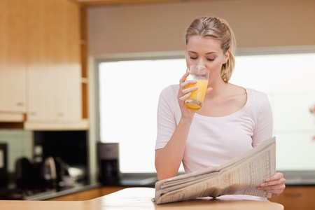 well read: Young woman reading the news while drinking orange juice in her kitchen