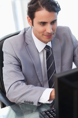 Portrait of a young businessman working with a computer in his office photo