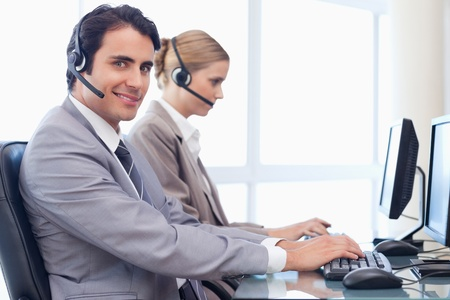 Smiling operators using a computer in a call center Stock Photo - 11685114