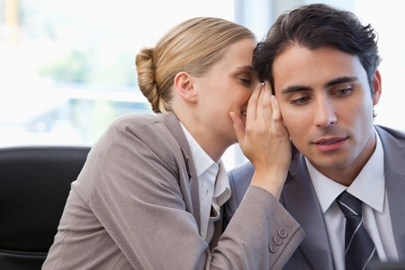 Businesswoman whispering something to her colleague in a meeting room photo