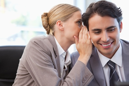 Young businesswoman whispering something to her colleague in a meeting room photo