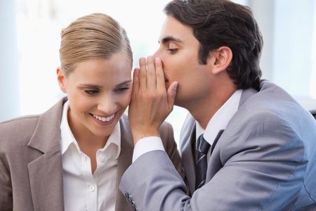 Businessman whispering something to his colleague in a meeting room photo
