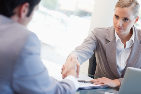 Serious manager interviewing a male applicant in her office photo