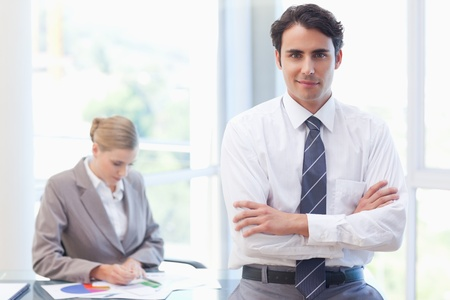 Young businessman posing while his colleague is working in a meeting room