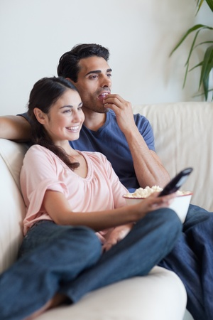 Portrait of a couple watching TV while eating popcorn in their living room photo