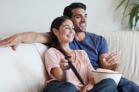 pareja viendo tv: Pareja mirando la televisi�n mientras come palomitas de ma�z en su sala de estar