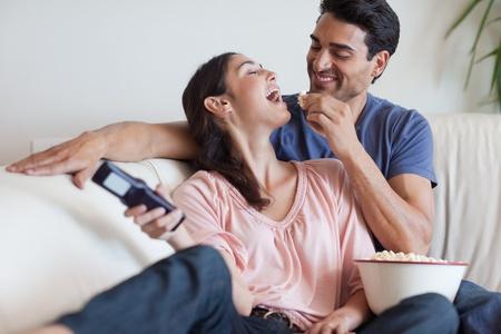 pareja viendo tv: Pareja juguetona viendo la televisión mientras come palomitas de maíz en su sala de estar
