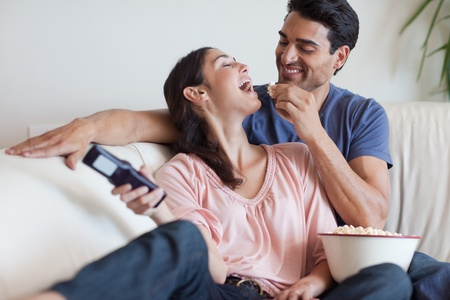 love movies: Playful couple watching TV while eating popcorn in their living room