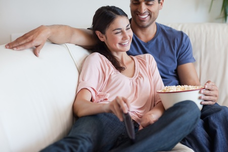 watching movie: Delighted couple watching TV while eating popcorn in their living room Stock Photo