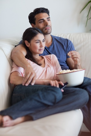 Portrait of a couple watching television while eating popcorn in their living room Stock Photo - 11682759