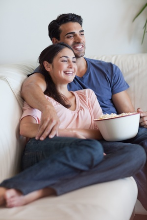 Portrait of a happy couple watching television while eating popcorn in their living room Stock Photo - 11682612