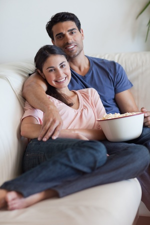 Portrait of a smiling couple watching television while eating popcorn in their living room Stock Photo - 11682857