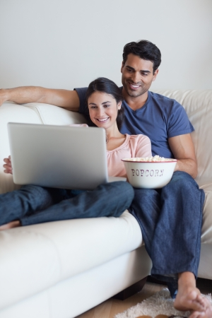 Portrait of a couple watching a movie while eating popcorn with a laptop photo