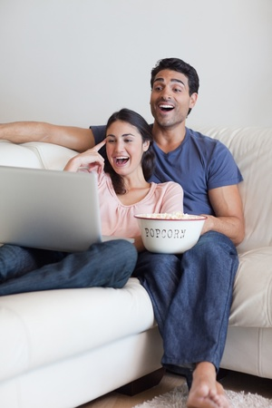 Portrait of a laughing couple watching a movie while eating popcorn with a laptop photo